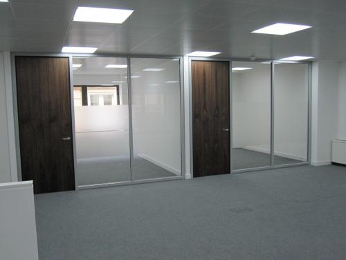 Glass partition system with walnut veneered doors